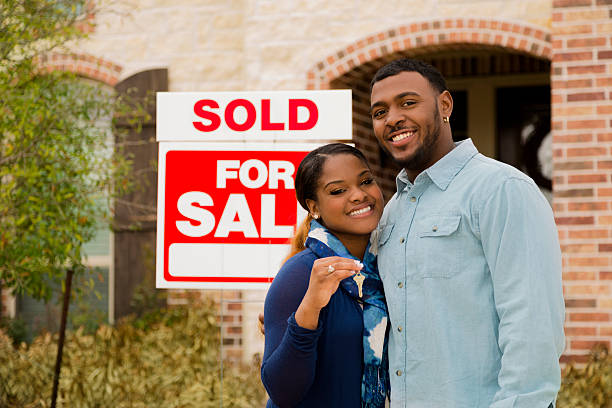 Real Estate: African descent couple buys first home. House key. African descent couple shows off key after purchasing a new home. 'Sold',  'For Sale' sign in background. Front entrance of this beautiful brick and stone home.  yes single word stock pictures, royalty-free photos & images
