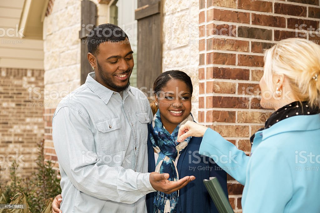 Real Estate: African descent couple buys home. House key, realtor. stock photo