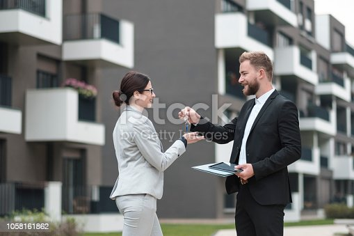Real estate agent and businesswoman customer, Image taken at average residential area with multiple ownership block of flats type of buildings.