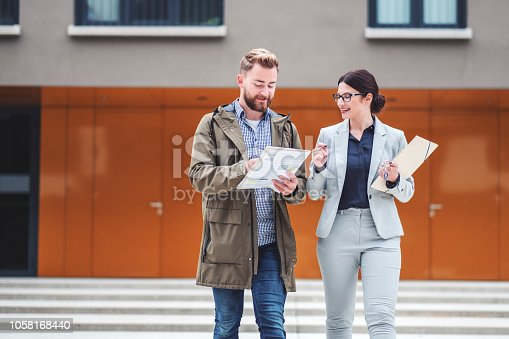 Real estate agent and customer looking for apartment. Image taken at average residential area with multiple ownership block of flats type of buildings.
