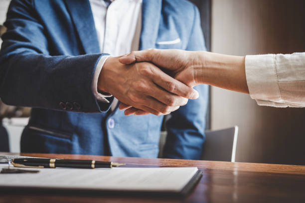 real estate agent and customers shaking hands together celebrating finished contract after about home insurance and investment loan, handshake and successful deal - vendere foto e immagini stock