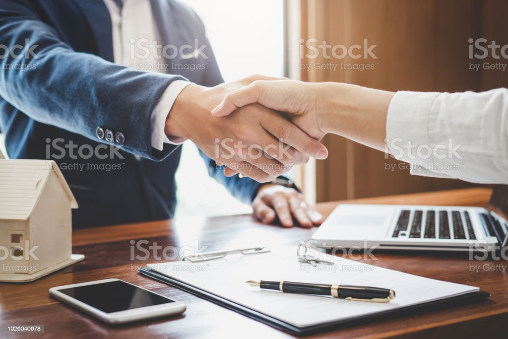 Real estate agent and customers shaking hands together celebrating finished contract after about home insurance and investment loan, handshake and successful deal Real estate agent and customers shaking hands together celebrating finished contract after about home insurance and investment loan, handshake and successful deal. Adult Stock Photo