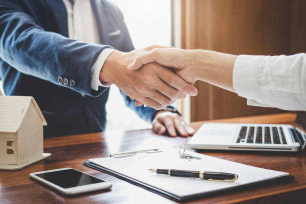 real estate agent and customers shaking hands together celebrating finished contract after about home insurance and investment loan, handshake and successful deal - handshake stock pictures, royalty-free photos & images