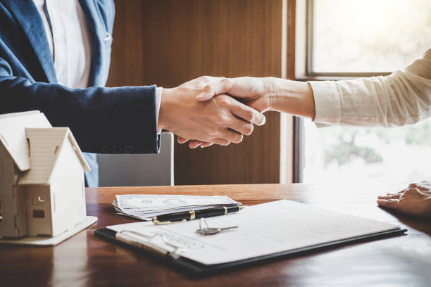 real estate agent and customers shaking hands together celebrating finished contract after about home insurance and investment loan, handshake and successful deal - real estate law stock photos and pictures