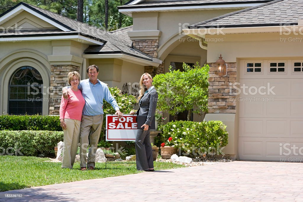 Real estate agent and senior couple by For Sale sign royalty-free stock photo