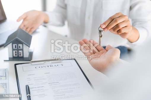 481337750 istock photo Real estate agent broker give a key with house sign contract. 1262564135