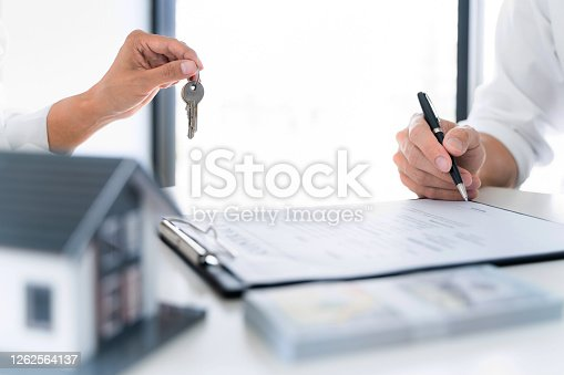 481337750 istock photo Real estate agent broker give a key with house sign contract. 1262564137