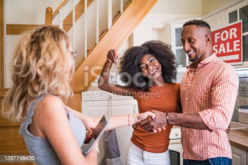 istock Real estate agent congratulating a new owner for buying new house 1257748420