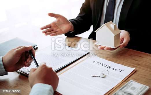 481337750 istock photo Real estate agent congratulations to new buyer by giving house model to client in the agency office. 1253376558