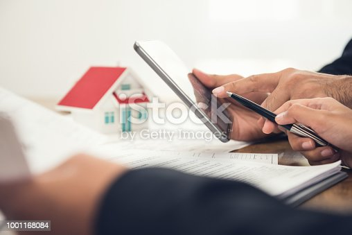 915688450 istock photo Real estate agent discussing information with client using digital tablet 1001168084