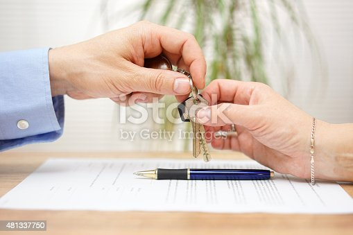 istock real estate agent gives house keys to his client 481337750