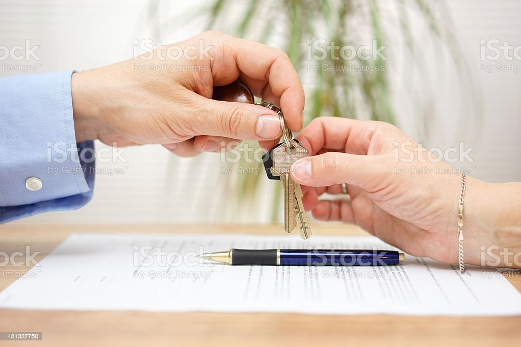 real estate agent gives house keys to his client stock photo