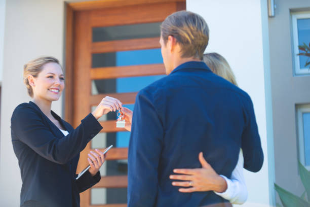 Immobilienmakler gibt einem jungen Ehepaar den Schlüssel zu ihrem neuen Haus. – Foto