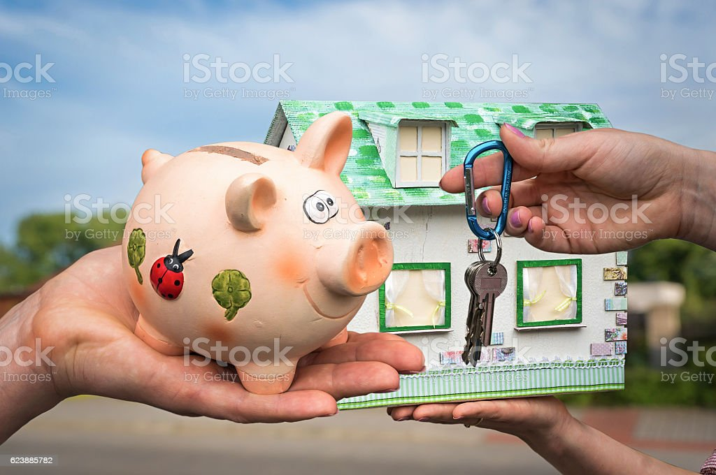 Real estate agent giving house key and model house stock photo
