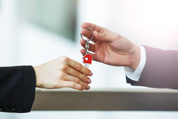 real estate agent giving house key to customer - imobiliaria imagens e fotografias de stock