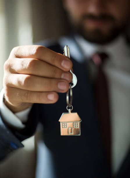 Real estate agent giving house keys stock photo