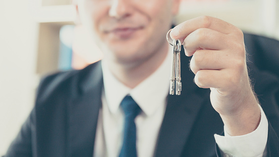 626187670 istock photo Real estate agent giving house keys to client. Property investment and financial mortgage 1201069727