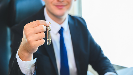626187670 istock photo Real estate agent giving house keys to client. Property investment and financial mortgage 1257153677