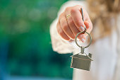 Real estate agent handing over the keys to a home. The key ring is house shaped. Copy space