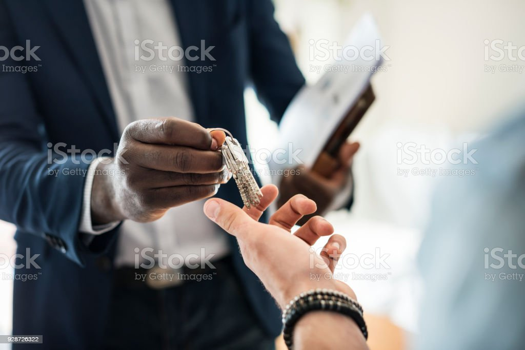 Real estate agent handing the house key to a client stock photo