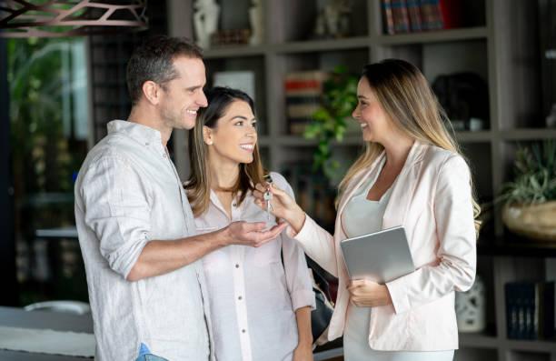 die schlüsselübergabe an die kunden in ihrem neuen zuhause, während sie eine tablette hält immobilienmakler - immobilienmakler stock-fotos und bilder