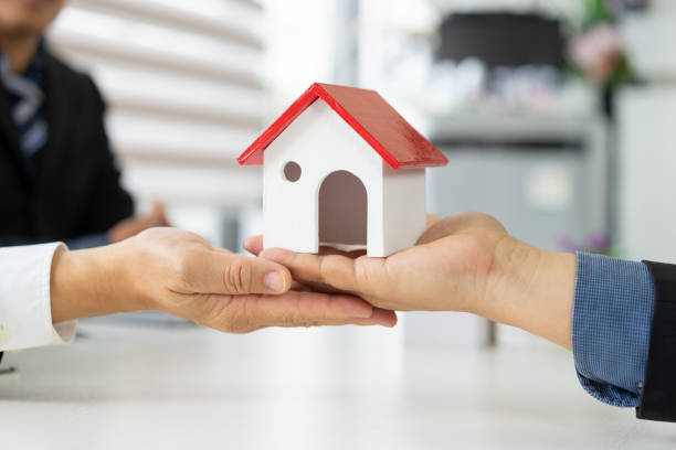 real estate agent hands offer house to buyer.home buying or house rental concept. - real estate law stock photos and pictures