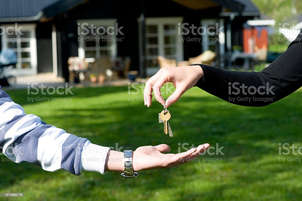 Real estate agent hands over keys over to new owner stock photo