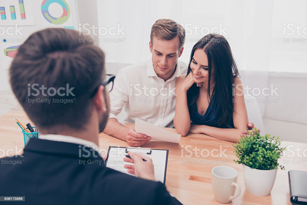 Real estate agent helping young family to buy flat - foto de stock