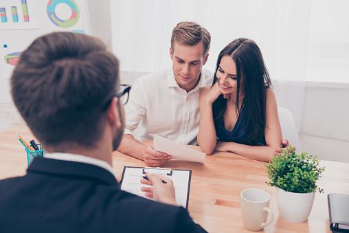 Real Estate Agent Helping Young Family To Buy Flat Foto de stock y más banco de imágenes de Abogado