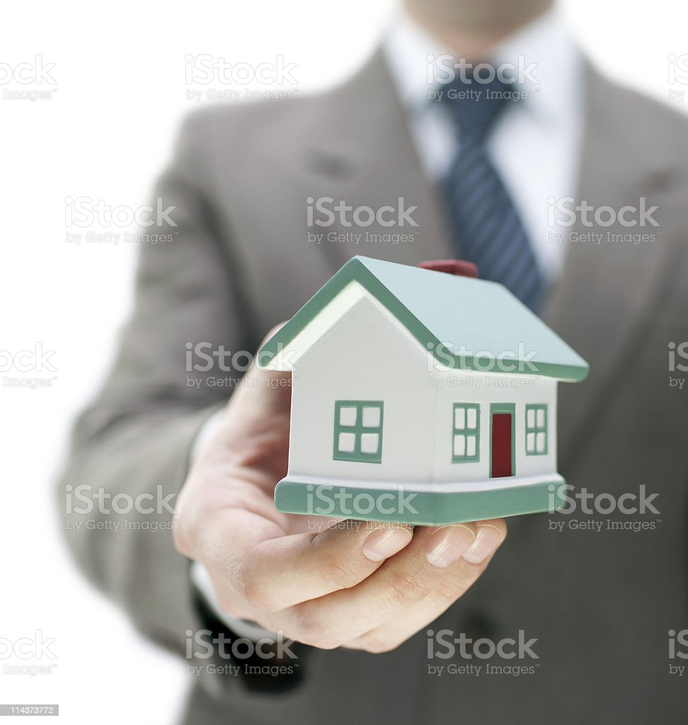 Real estate agent holding a toy house royalty-free stock photo