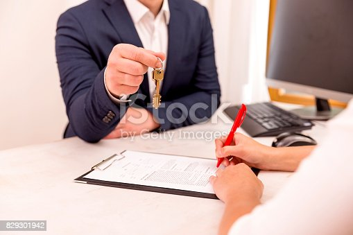 istock Real estate agent holding house key to his client after signing contract,concept for real estate, moving home or renting property 829301942