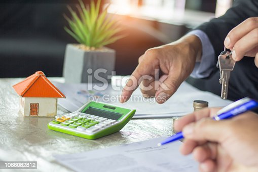real estate agent holding house key to his client after signing contract agreement in office,concept for real estate, renting property