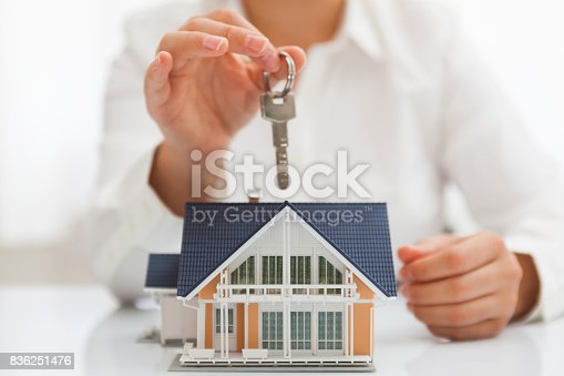 828544458istockphoto Real estate agent holding key with house model 836251476