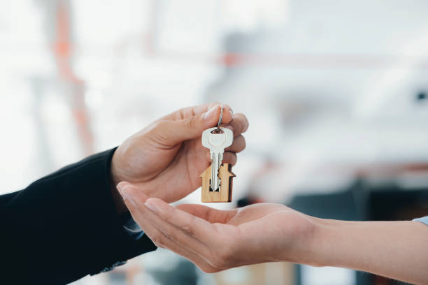 Real estate agent  holding key with house shaped keychain. stock photo
