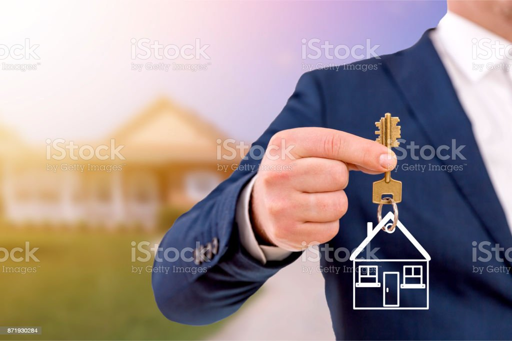 Real estate agent holding keys in front of a beautiful new home. stock photo