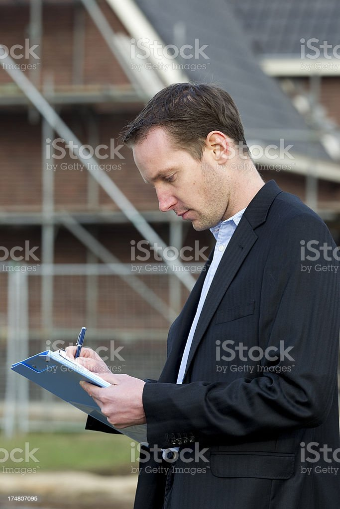 Real estate agent in front of house building stock photo