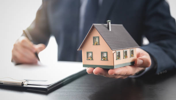 Real estate agent is holding a house model stock photo