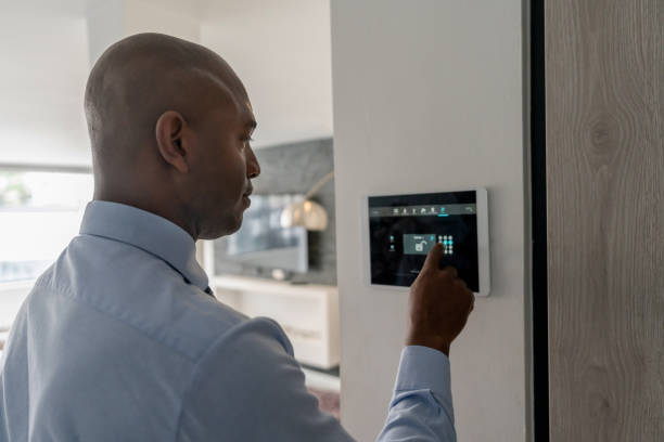 Real estate agent locking the door of a house using a home automation system stock photo