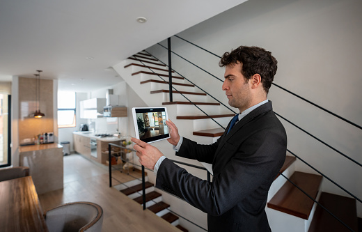 Latin American real estate agent making a virtual tour of a house using a tablet computer - real estate concepts
