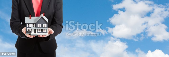 istock Real Estate Agent Offering Dream Home Against Blue Sky Billboard 505726407