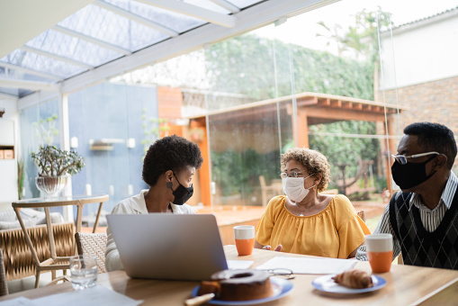Real estate agent on a meeting with senior couple at home - wearing face mask