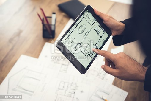 istock Real estate agent or architect presenting house floor plan to client on tablet computer 1137648354