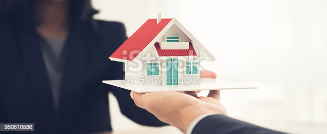 istock Real estate agent or architect presenting house model to client 950510536