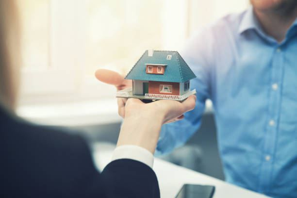 real estate agent or architect presenting house model to customer - imobiliaria imagens e fotografias de stock