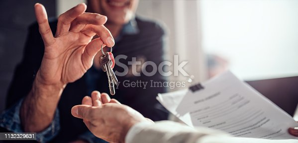 Real estate agent sitting at the desk by the window and passing keys to his client in the office