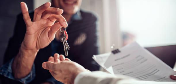 agente imobiliário que passa chaves a seu cliente - chave - fotografias e filmes do acervo