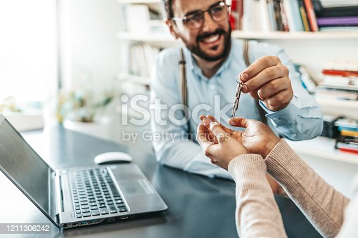 Happy male estate agent giving house keys to a woman as agreement in office