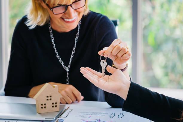 Immobilienmakler legt Schlüssel auf die Hand – Foto