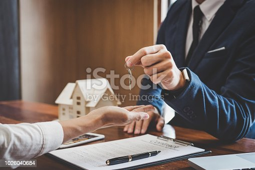istock Real estate agent Sales manager holding filing keys to customer after signing rental lease contract of sale purchase agreement, concerning mortgage loan offer for and house insurance 1026040684