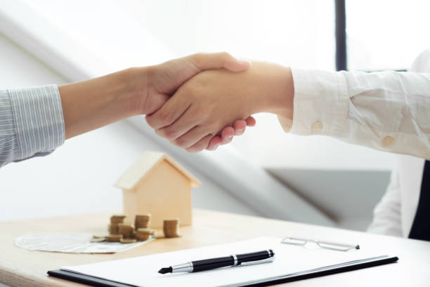 real estate agent shaking hands with client about property contract. - real estate law stock photos and pictures